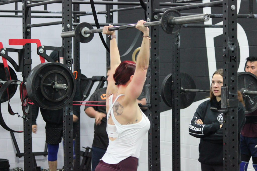 Woman performing an overhead press while strength training under the supervision of her coach