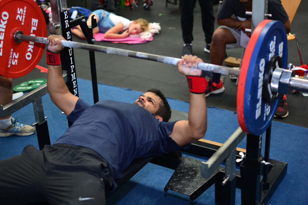 A lifter bench pressing in competition using wrist wraps